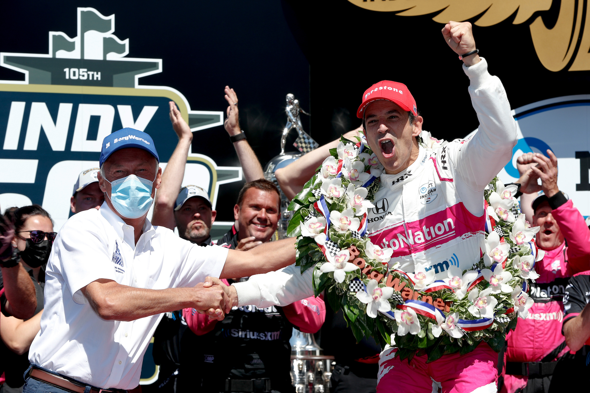 Man in blue hat shakes hand of man in pink hat with celebratory wreath with crowd in background