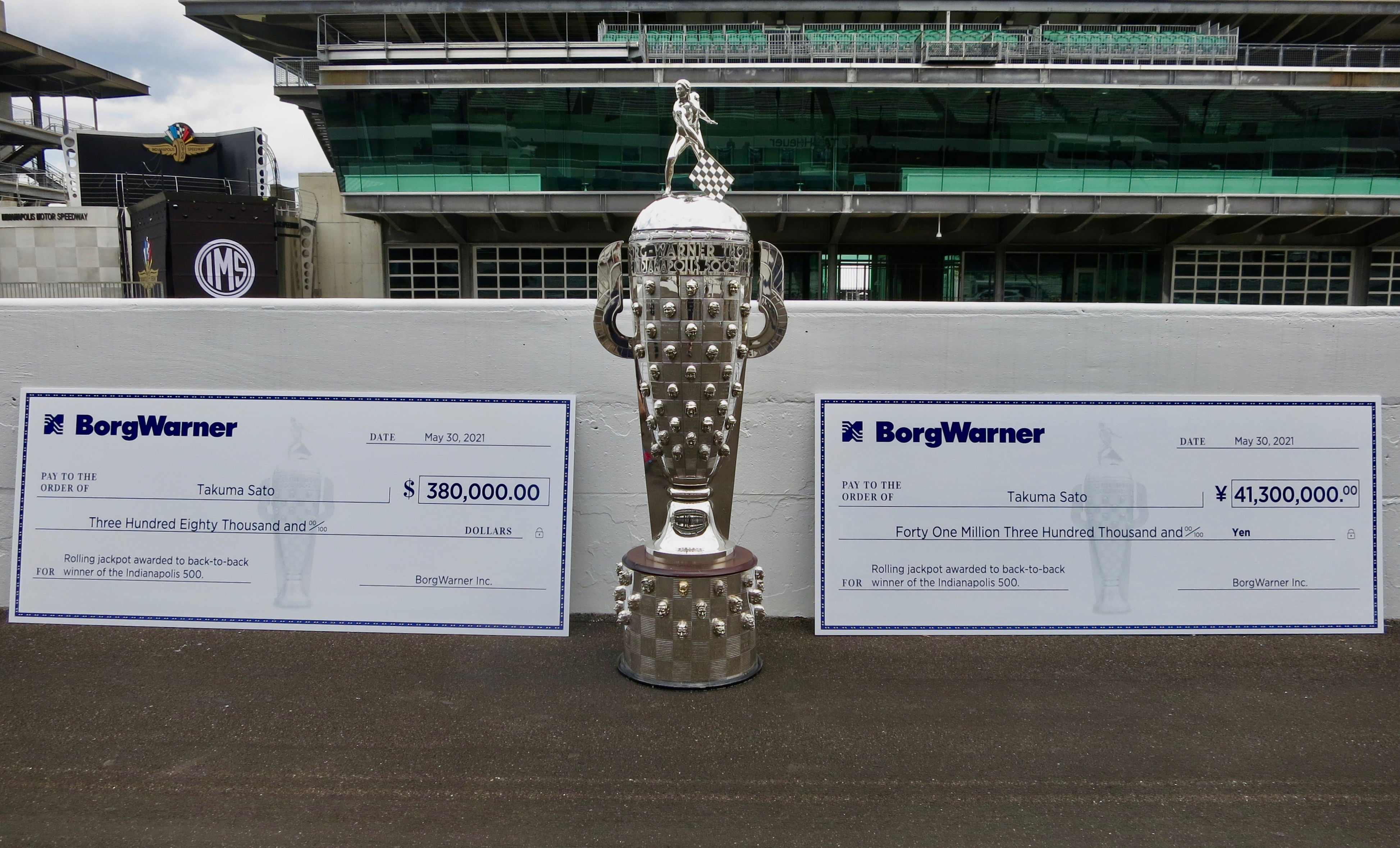 Large silver trophy with two large checks on either side on race track with stands in background