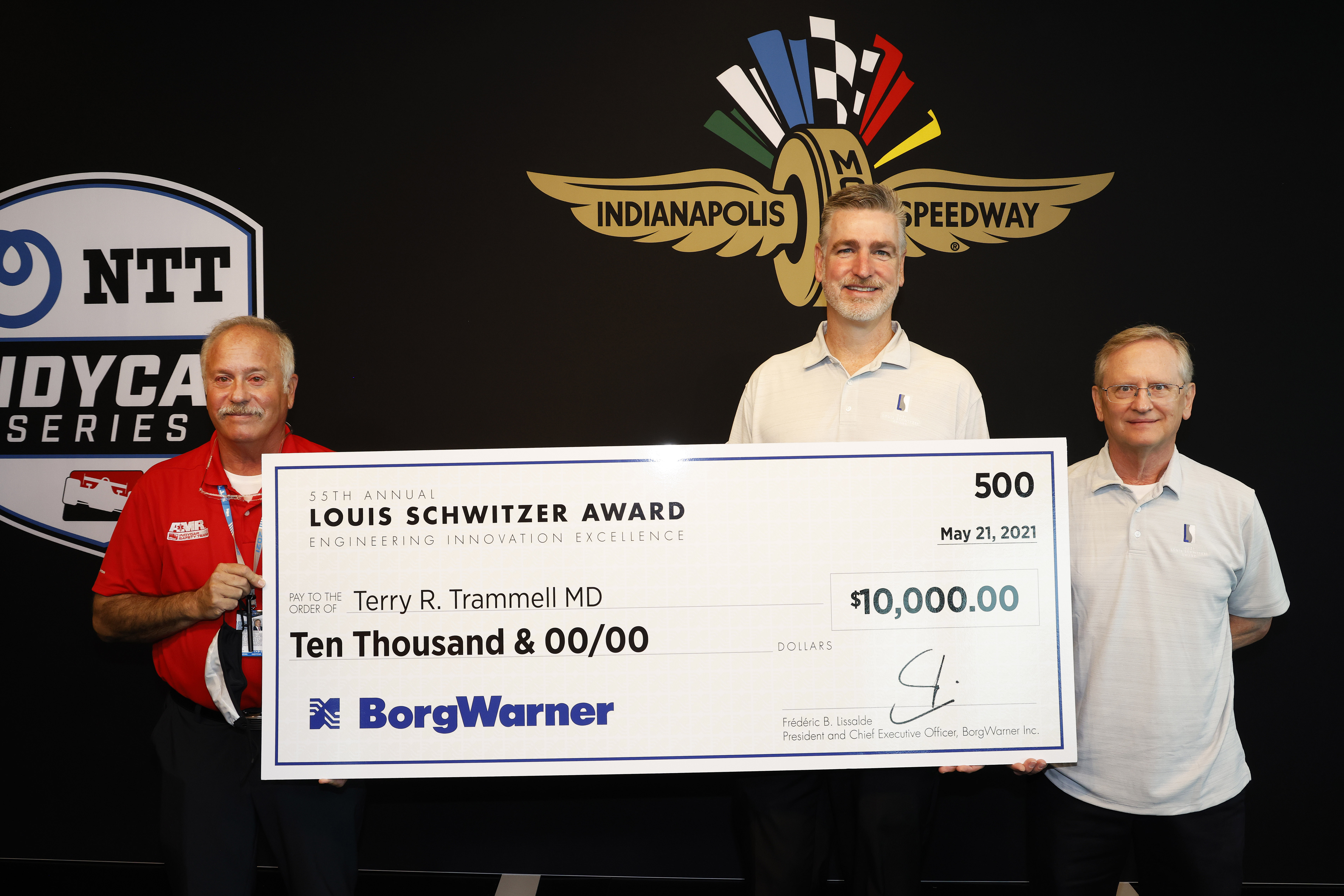 Three men hold large check against black logo backdrop