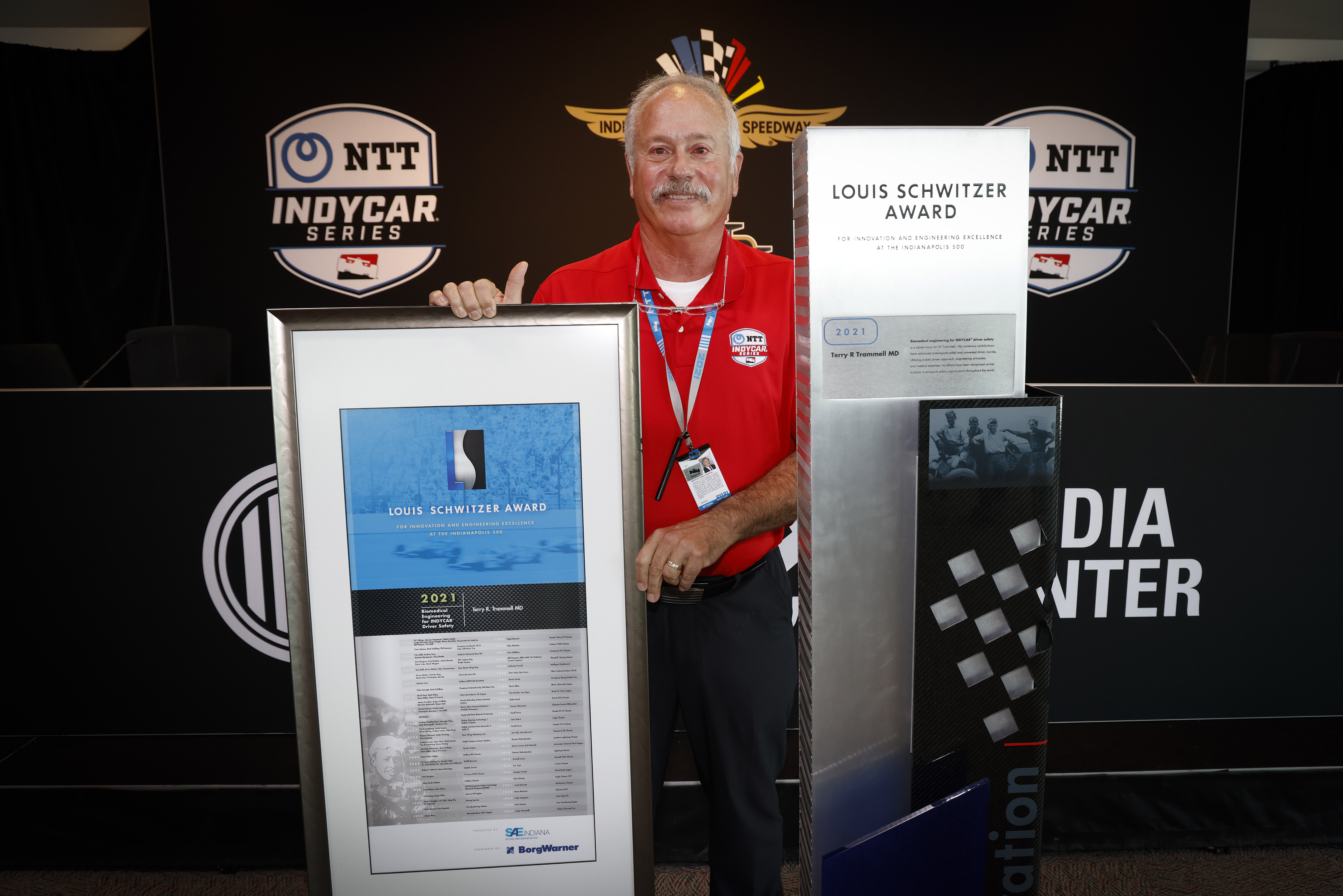 Man stands with large plaque against black logo backdrop