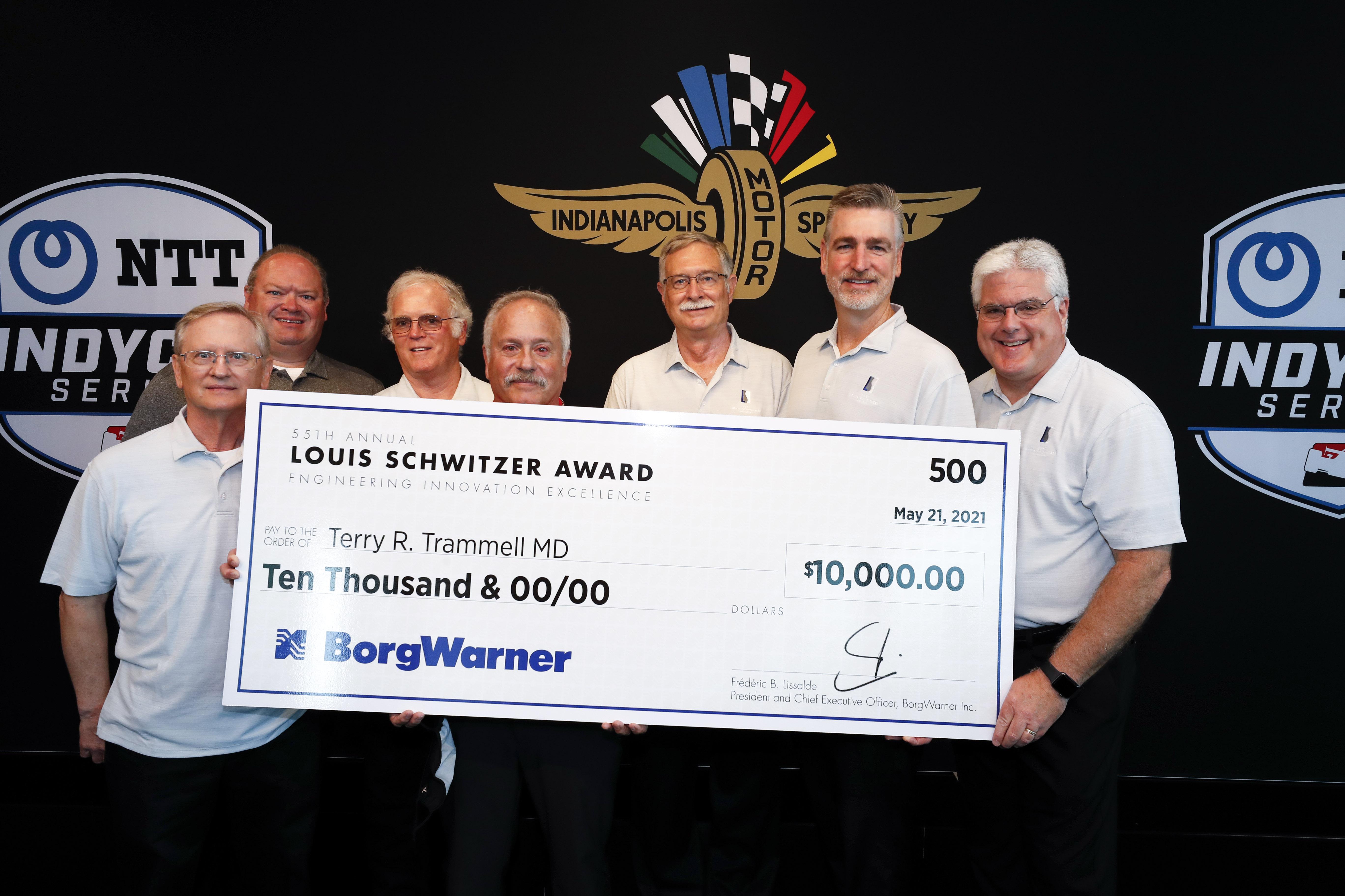 Seven men hold large check against black logo backdrop
