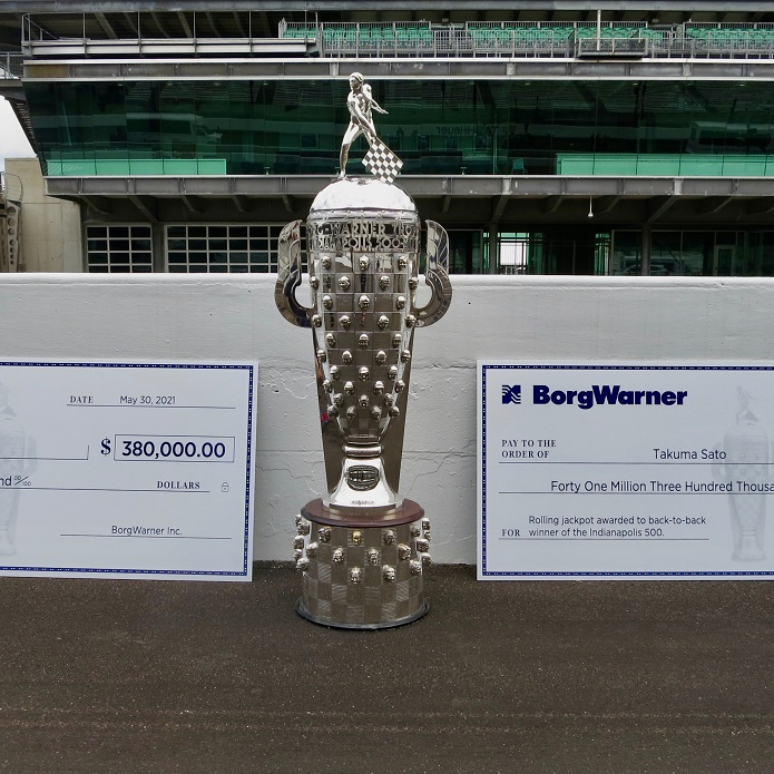 Large silver trophy and two oversized checks sitting on either side of it on race track