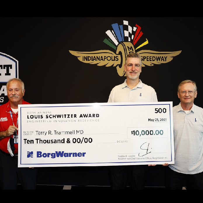 Three men stand holding large check in front of black logo backdrop